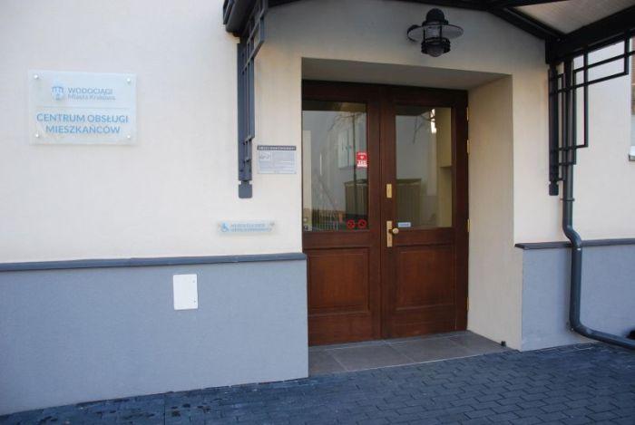 Wejście z drugiej strony budynku: przeszklone, szerokie drzwi, tabliczka z logo WMK S.A. oraz z napisem Centrum Obsługi Mieszkańców.