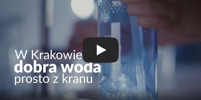 Kadr z filmu o Wodociągach Miasta Krakowa z czarną ikoną YouTube na środku. W tle widać bidon napełniany wodą z kranu oraz z napisem: W Krakowie dobra woda prosto z kranu