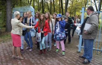 Przez bramę wejściową wchodzi grupa młodzieży. Przed nimi stoi kobieta obok mężczyzna.