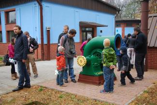 Przed niebieskim budynkiem stoją  dzieci i dorośli. Patrzą na zabytkowy zielony fragment pompy wodociągowej.