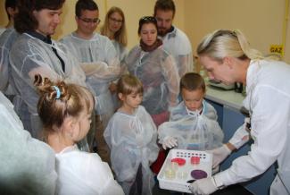 Gromadka dzieci oraz dorośli patrzą na Panią, która pokazuje próbki laboratoryjne. Wszyscy ubrani w w białe fartuchy.