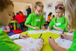 Dzieci rysują na leżących na stoliczku kartkach. Z tyłu widać Panią stojącą przodem do dużej, białej tablicy.