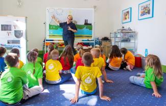 Dzieci w kolorowych podkoszulkach siedzą na dywanie. Patrzą na Panią, która pokazuje ręką na obrazek. Widać na nim chmury, rzekę i słońce.