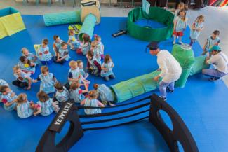 W sali na podłodze bawią się dzieci ubrane w niebieskie pluszowe kamizelki. Wchodzą do tunelu imitującego długą rurę.