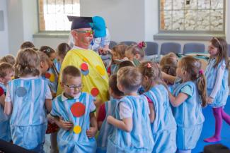 W sali stoi mężczyzna w żółtym ubraniu i czapce akademickiej. Robi śmieszną minę. Wokół niego dzieci przebrane za kropelki.