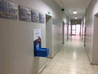 Korytarz szkolny. Na ścianie po lewej stronie zawieszony niebieski pitnik.