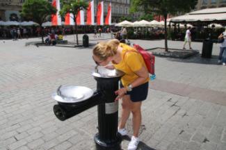 Płyta Rynku w Krakowie. Dziewczyna w żółtym podkoszulku pije wodę z pitnika.