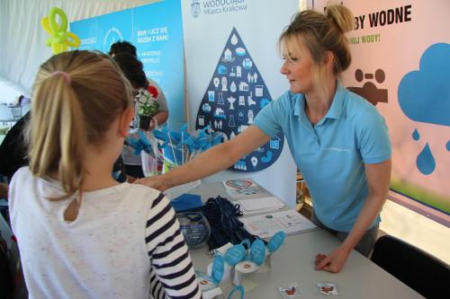 Kobieta w niebieskiej koszulce wyciąga rękę do dwóch dziewczynek. Na stole ulotki i gadżety. Z tyłu roll up z logo kampanii.