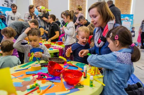 Wnętrze budynku. Kobieta z trójką dzieci siedzi przy stoliku, na nim są kolorowe kartki i kredki.
