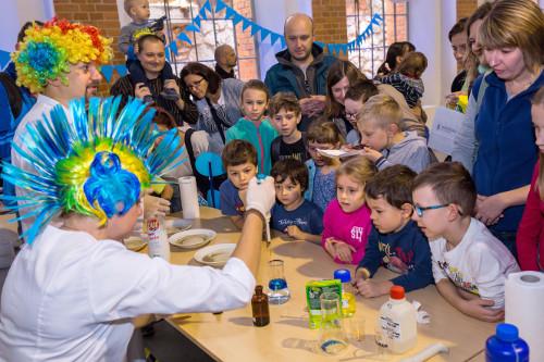 Wnętrze budynku. Dzieci i dorośli patrzą na pokazy chemiczne prowadzone przez osoby w białych fartuchach i kolorowych perukach.
