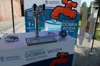 mobilny bar z dobrą wodą prosto z kranu, z tyłu reklama z grafiką kampanii: pomarańczowy kran i szklanka.