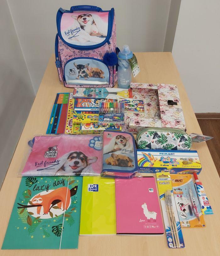 Stoł na którym położone są przybory szkolne: plecak, piórnik, zeszyty, kredki, długopisy, bloki, papiery kolorowe, farby, plastelina.