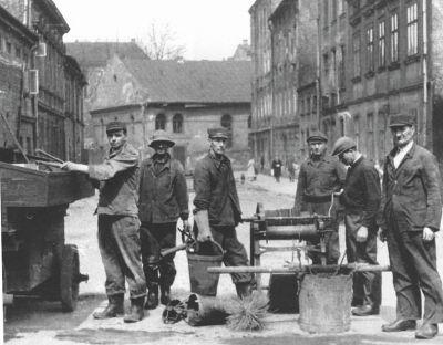 Pracownicy podczas wykonywania obowiązków. Zdjęcie czarno białe.