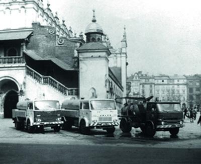Trzy samochody specjalistyczne na tle sukiennic na płycie Rynku Głównego. Zdjęcie czarnobiałe.