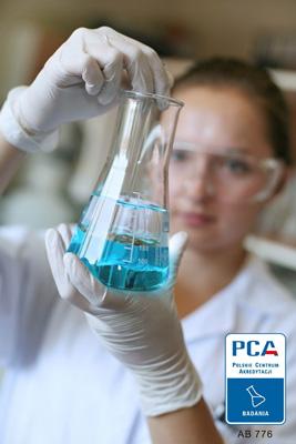 Laborantka w odpowiednim ubraniu ochronnym trzyma fiolkę z niebieskim płynem.