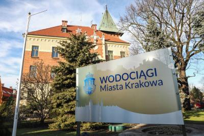 Tablica z napisem Wodociągi Miasta Krakowana na tle budynku-siedziby spółki.