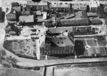 Widok z lotu ptaka na Siedzibę Główną Wodociągów Miasta Krakowa na starej czarno-białej fotografii.