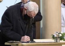 Pochylony Prezydent Jacek Majchrowski podpisuje akt nadania sztandaru.