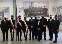 Pamiątkowe zdjęcie Zarządu z pocztem sztandarowym na tle zabytkowej wystawy i historycznego zdjęcia.