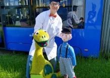Dziadek Tadek, kukiełki wnuczek Olek i smok stoją przed tramwajem.