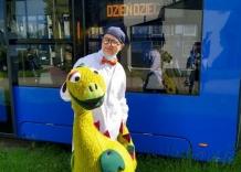 Dziadek Tadek i kukiełka smoka stoją przed niebieskim tramwajem.