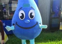 Niebieska Kropelka stoi przed niebieskim tramwajem