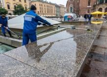 Pracownicy za pomocą szczotek czyszczą fontannę na Rynku Głownym.