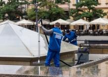 Dwaj pracownicy Wodociągów Miasta Krakowa czyści fontannę na Rynku Głównym w Krakowie.