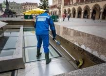 Pracownik Wodociągów Miasta Krakowa odwrócony tyłem czyści fontannę.
