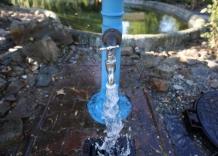 Hydrant z pokrętłem. Lejąca się woda.