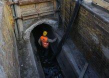 Pracownik podczas pracy remontowej w kanale otwartm na Bulawarch Wiślanych. Zdjęcie współczesne.