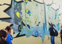 Młodzież wskazuje na kolorowy mural umieszczony na ścianie jednego z reaktorów oczyszczalni ścieków Płaszów.