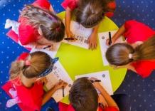 Dzieci przy okrągłym stoliku rozwiązują krzyżówki podczas zajęć Akademia Kropelki.