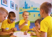 Dzieci wspólnie rysują przy stoliku podczas zajęć Akademia Kropelki.