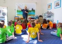 Prowadząca zajęcia Akademia Kropelki tłumaczy dzieciom obieg wody w przyrodzie.