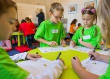 Dzieci siedzą przy stoliku i wykonują zadania podczas Akademii Kropelki.