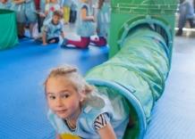 Dzieci przebrane za kropelki wody przechodzą przez imitację rur.