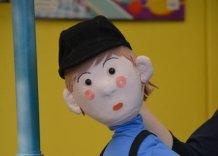 Maskotka wnuczka Olka w niebieskiej koszulce, w spodniach w paski z szelkami i z czarną czapką.