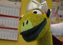 Maskotka przedstawiająca Smoka Skartka: zielonego, uśmiechniętego i w srebrnej koronie.